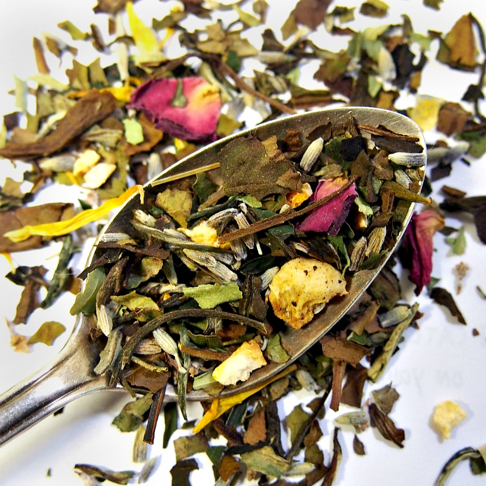 Overhead view of a spoon full of Lavender Dream loose leaf white tea with fruit and flower petals.
