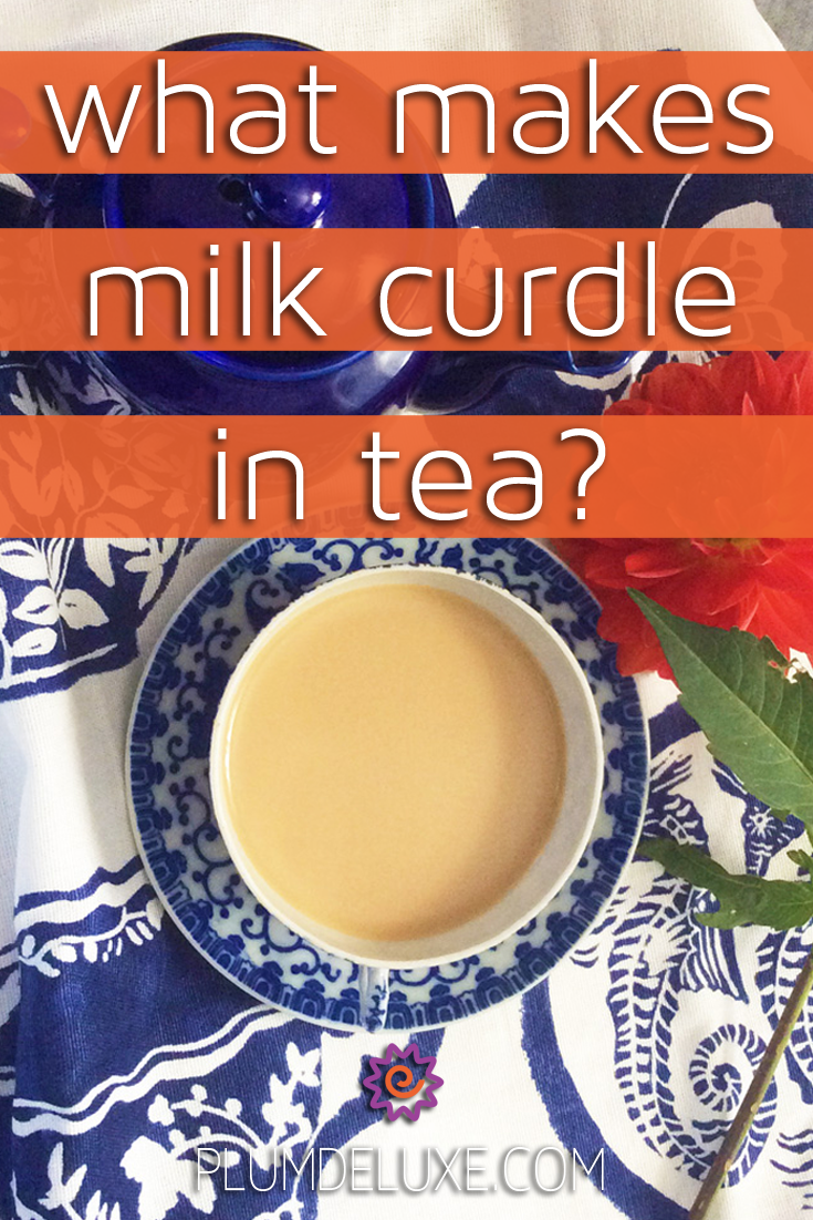 Overhead view of a blue and white teacup full of tea with milk, on a white and blue tea towel, next to a blue teapot and an orange flower with the words: what makes milk curdle in tea?