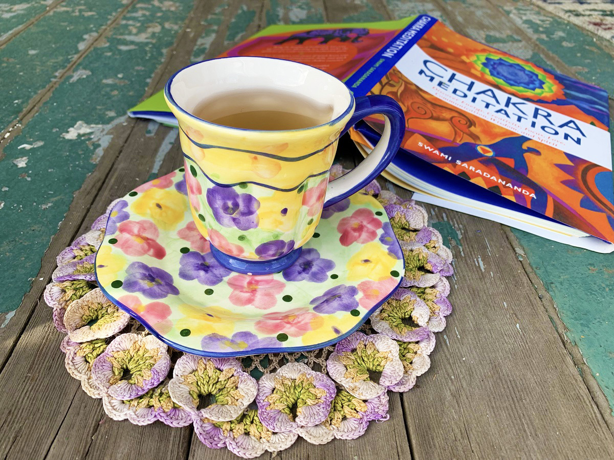 A brightly colored floral print teacup and saucer sit on a crochet floral coaster next to a chakra meditation book.