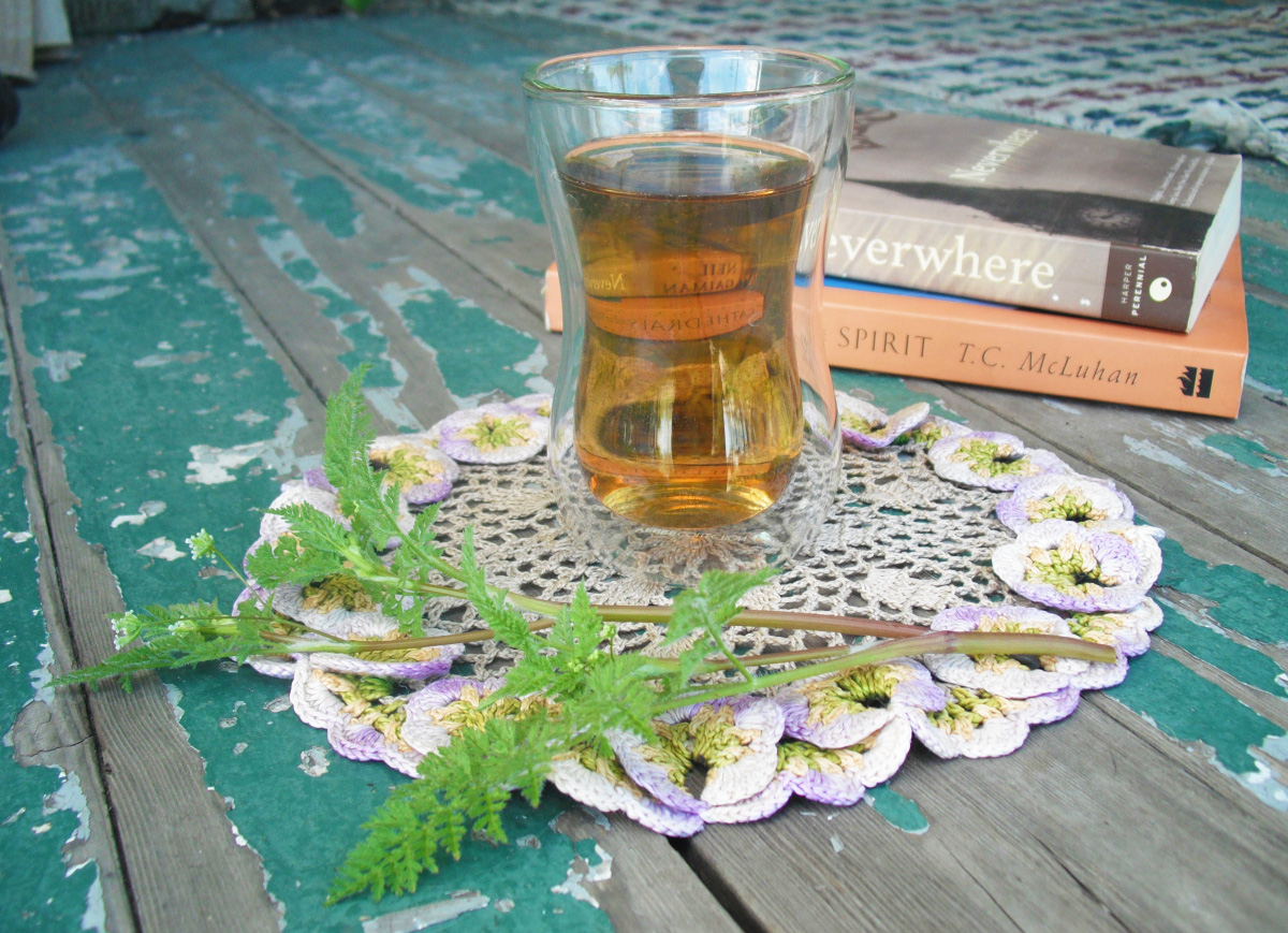 A clear, Turkish style glass full of iced tea sits on a crochet floral coaster in front of a stack of books.