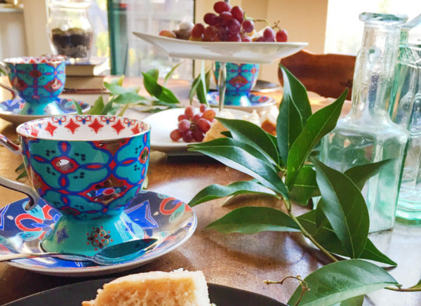 A brightly colored blue and red teacup with a geometric design sits on a table in the foreground, with a tiered tray of fruits and sweets and more teacups in the background.