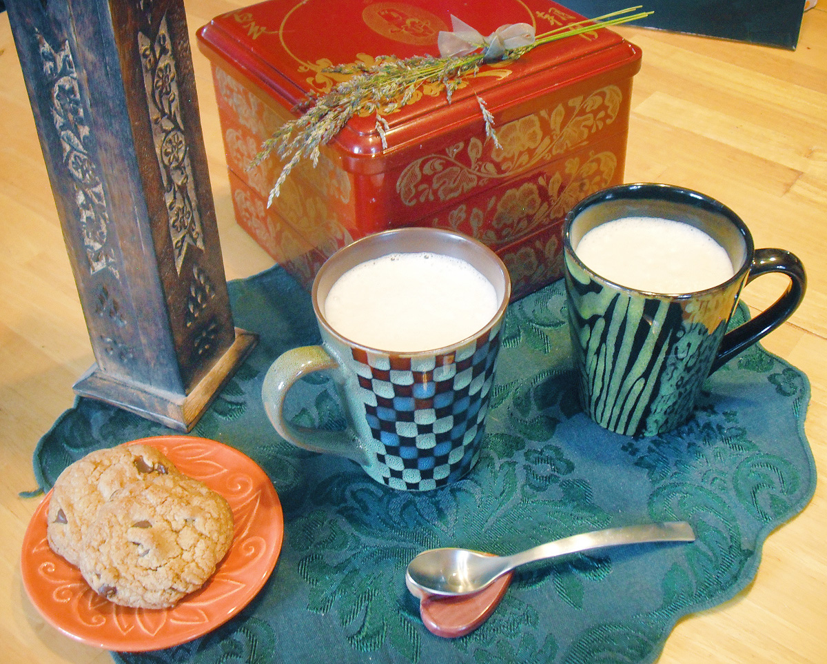 Two mugs of lavender tea latte sit on a green mat next to an orange plate of cookies. A red box with a bundle of lavender on it is in the background.