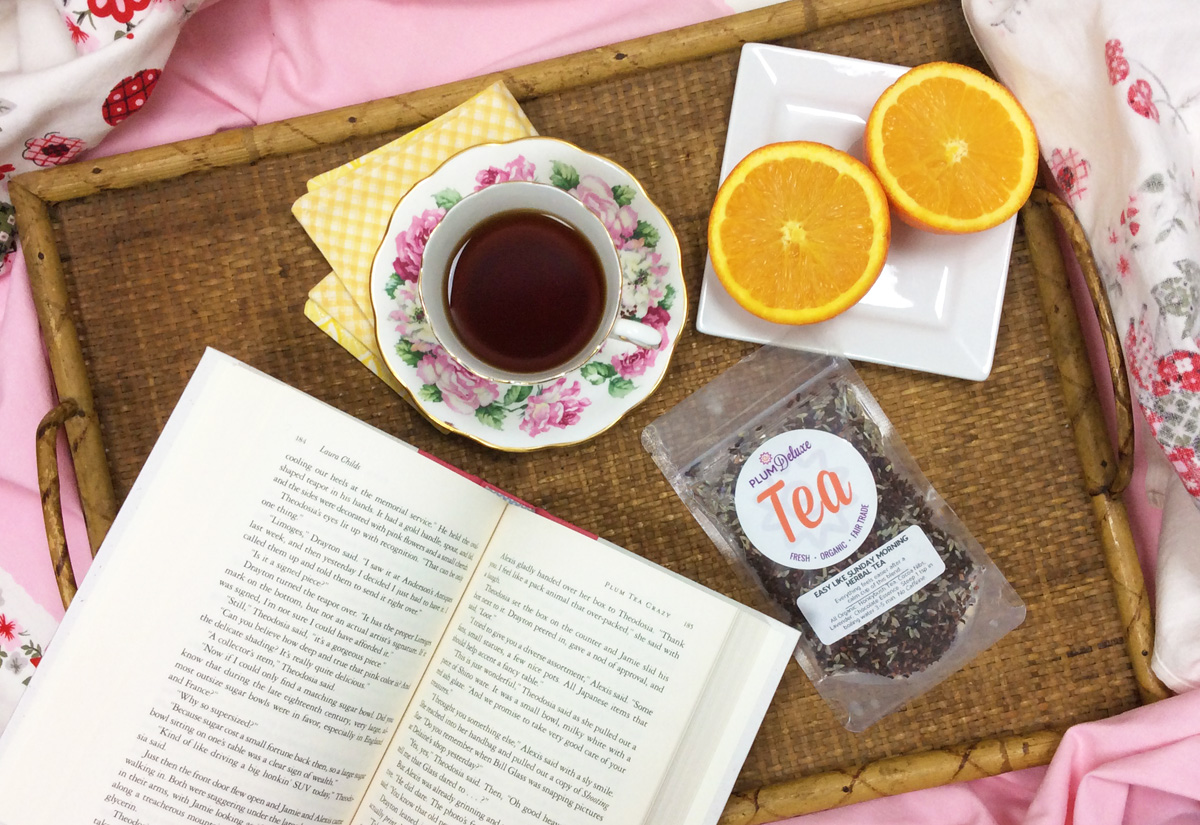 Overhead view of a woven tray with a book, cup of tea, halved orange, and bag of loose leaf lavender tea on a pink and floral sheet set.
