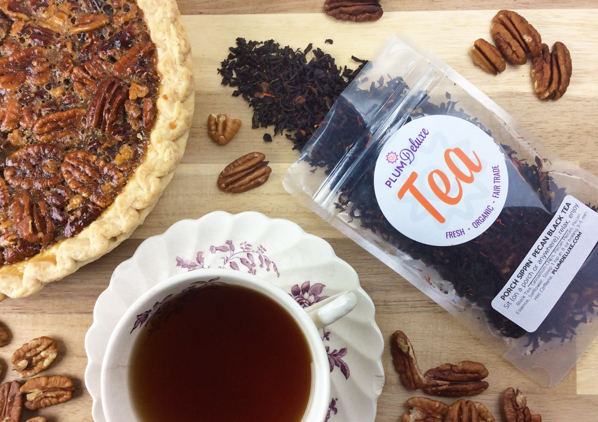 Overhead view of a bag of pecan black tea surrounded by pecans, a pecan pie, and a cup of brewed tea on a wooden table.