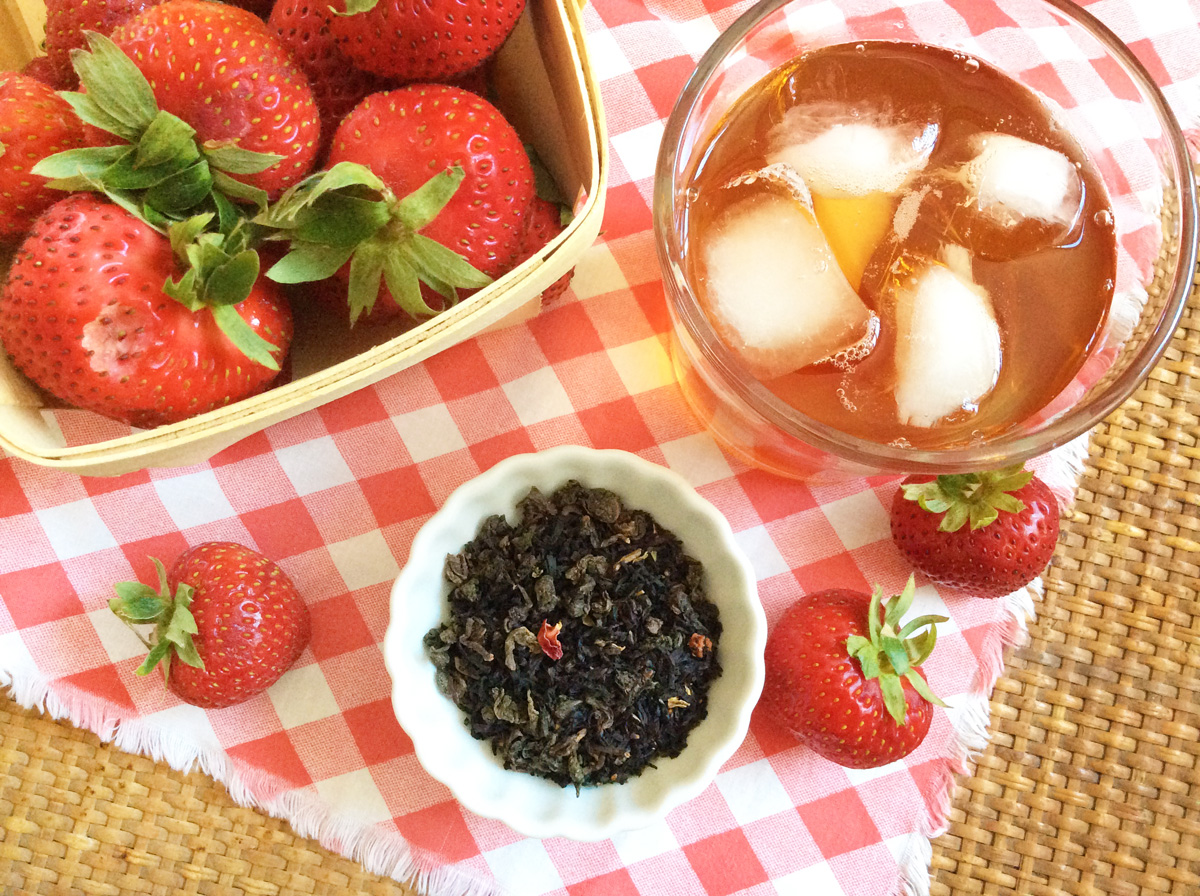 Overhead view of a glass of iced tea, basket of strawberries, and white dish of loose leaf tea on a red and white checkered cloth.