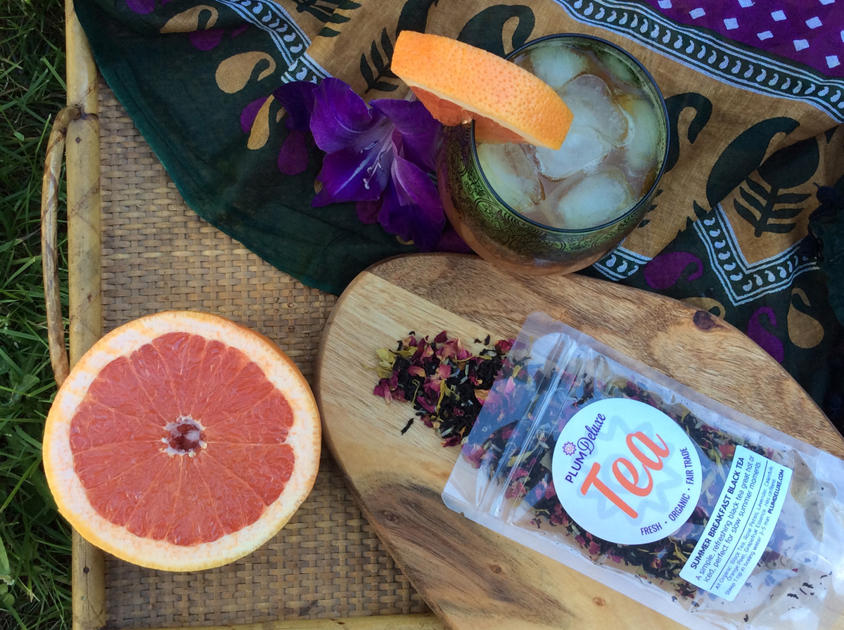 Overhead view of a glass of iced tea, half a grapefruit, and a bag of loose leaf tea on a wooden board with a colorful cloth on the side.