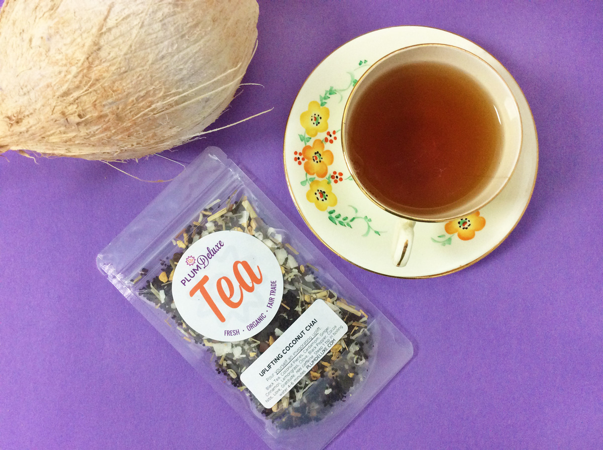 Overhead view of a bag of coconut chai next to a cup of tea and a coconut on a purple background.