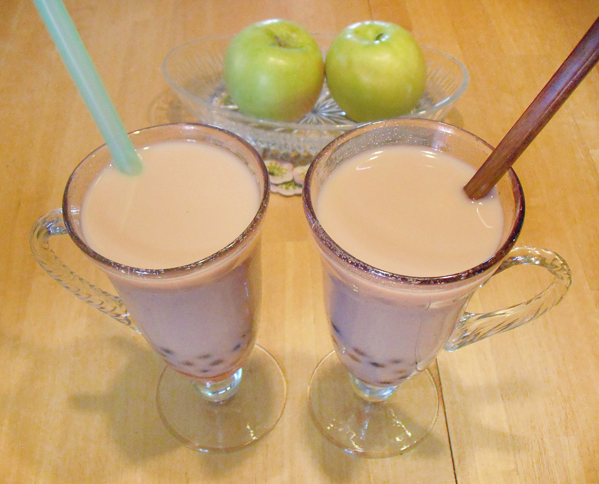Two glasses of bubble tea with straws sit on a wooden table with two green apples in the background.