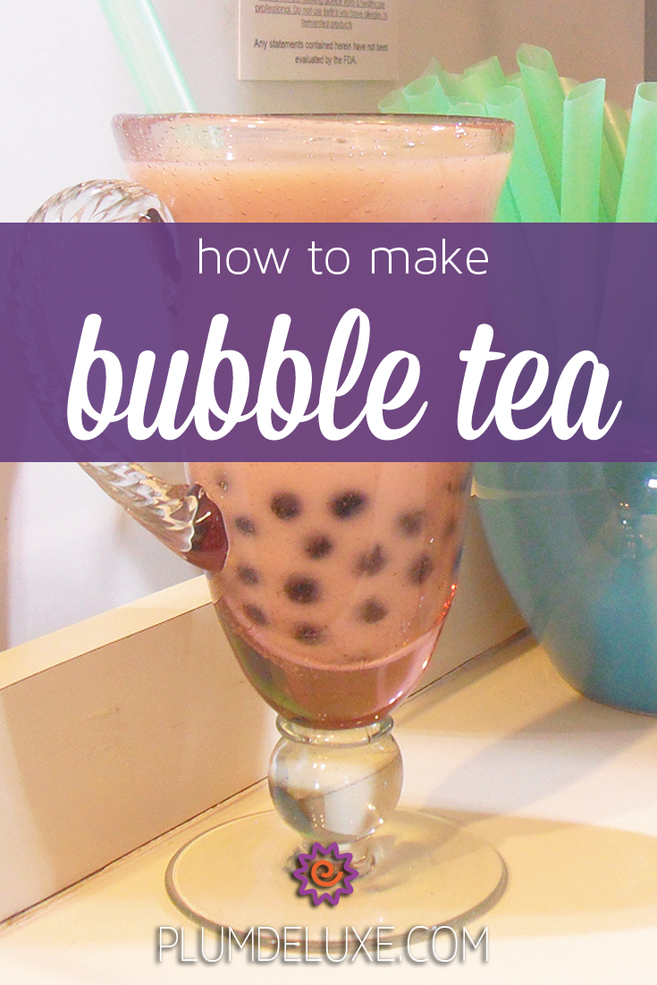 A glass of bubble tea with a green straw sits on a counter. The words say: how to make bubble tea.