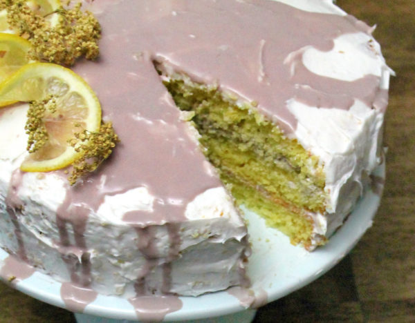 Closeup of a lemon elderberry cake with a slice cut out. You can see all three yellow cake layers with purple frosting in between.