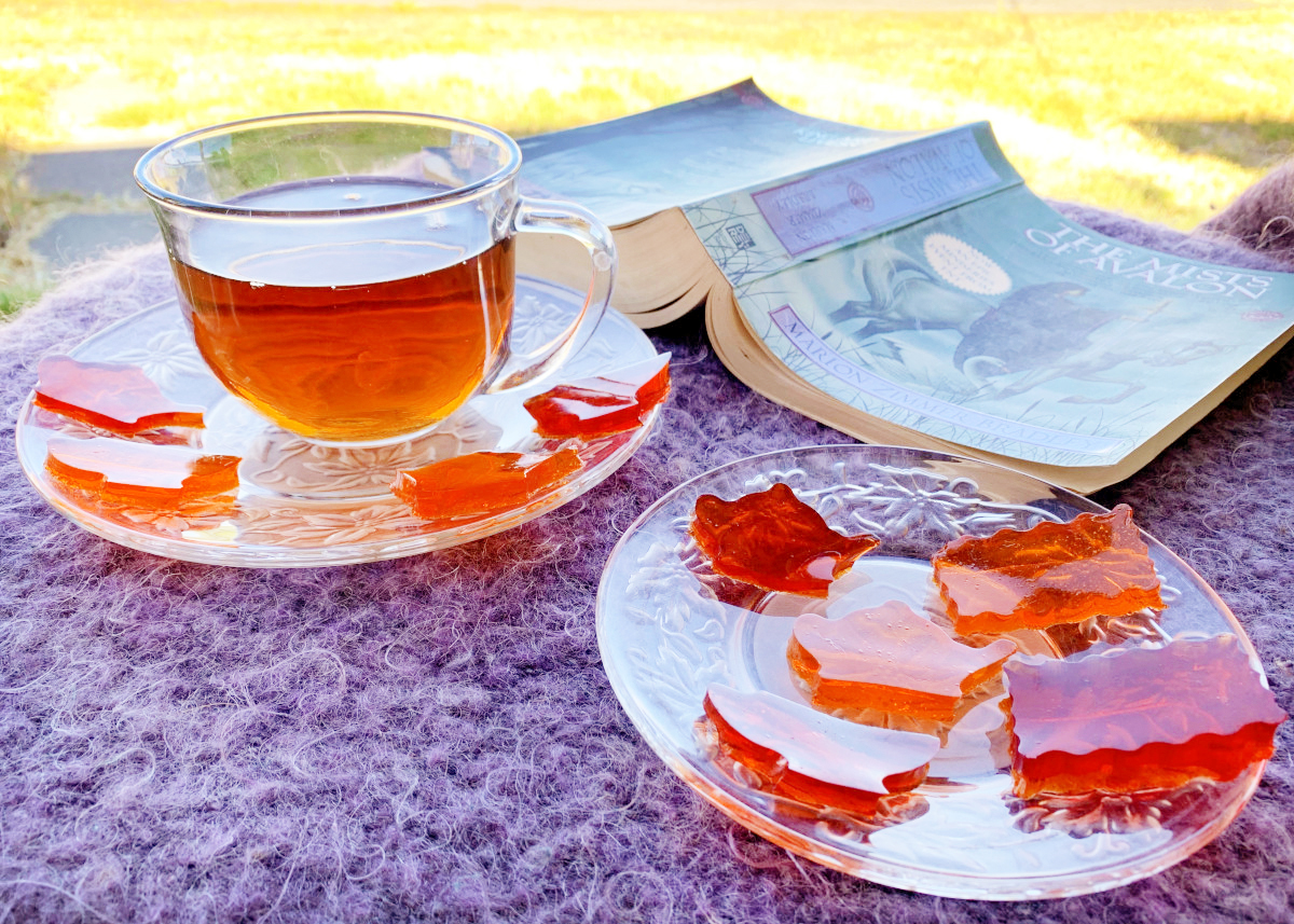 A clear glass cup of tea is surrounded by orange and red tea jello jigglers next to a thick book on a fuzzy purple blanket.