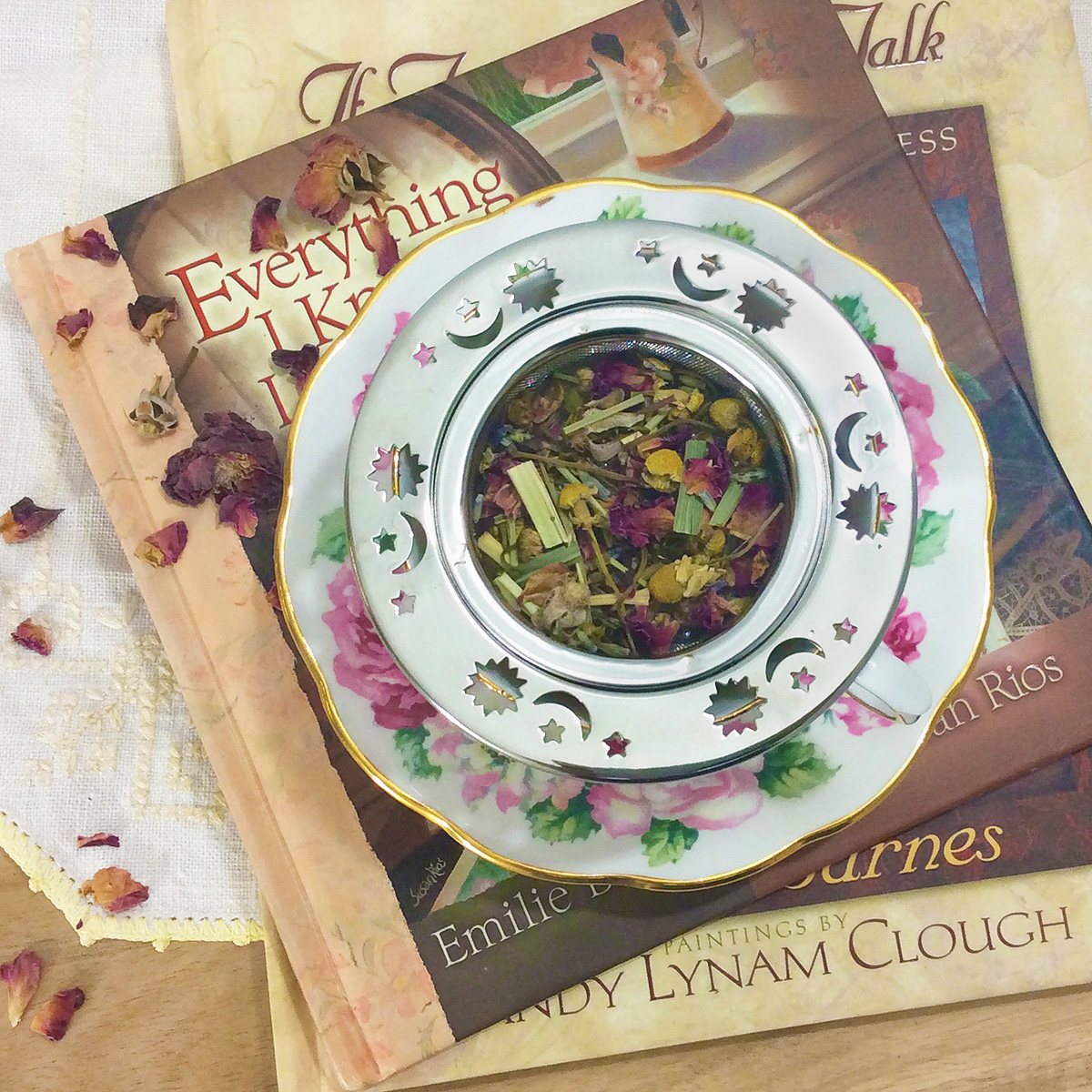 Overhead view of a rose patterned teacup with a celestial metal infuser full of chamomile rose tea. It rests on a small stack of books about tea.