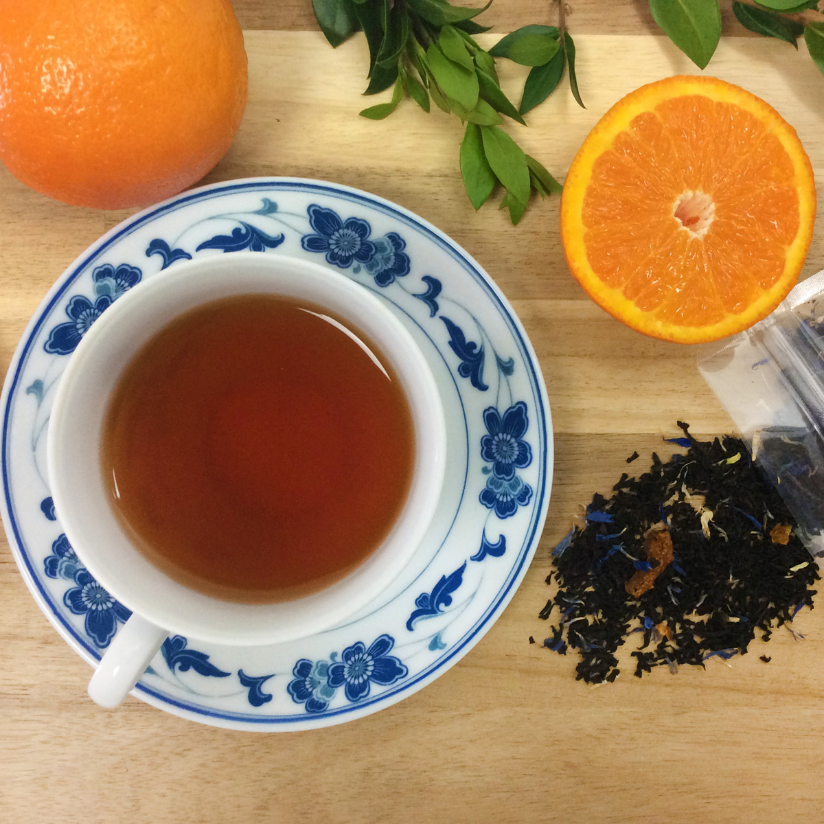 Overhead view of a white and blue teacup full of Earl Grey tea surrounded by loose leaf tea, oranges, and greenery on a wooden table.