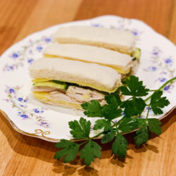 Three tea sandwiches are arranged on a white floral plate along with a sprig of parsley.