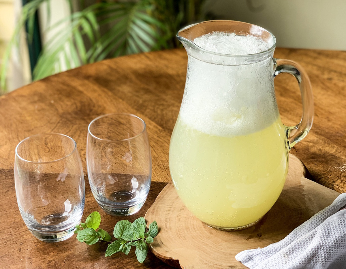 A clear glass pitcher of pineapple agua fresca sits on a wooden slab next to two empty glasses and several sprigs of fresh mint.