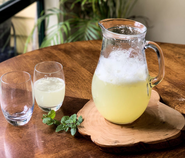 A clear glass pitcher of pineapple agua fresca sits on a wooden slab next to a glass of agua fresca and several sprigs of fresh mint.