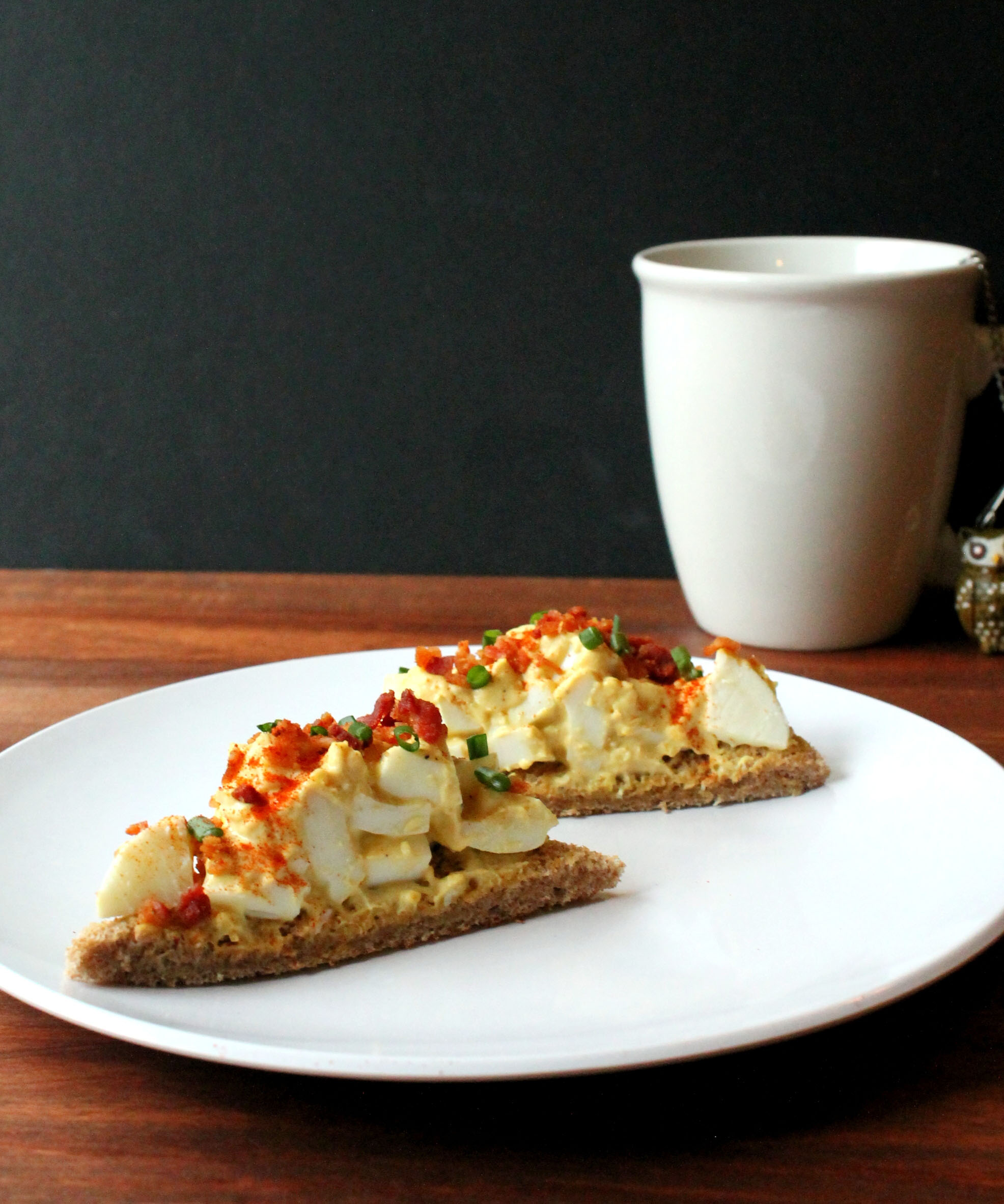 Two wedges of open-faced egg salad tea sandwiches sit on a white plate with a white mug of tea in the background.