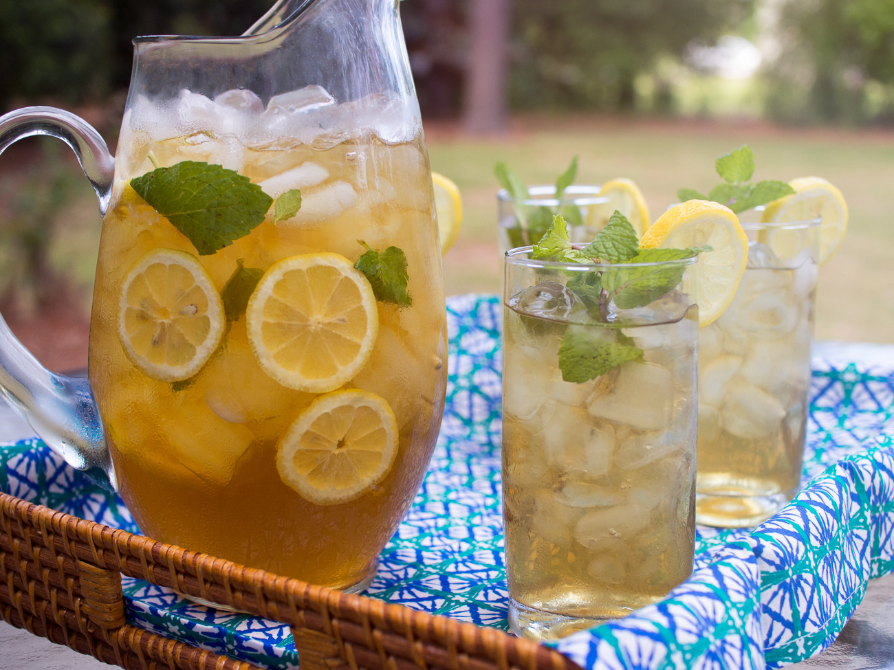 A glass pitcher of iced tea and lemons sits next to a tall glass full of tea and ice on a woven tray with a bright blue patterned cloth.