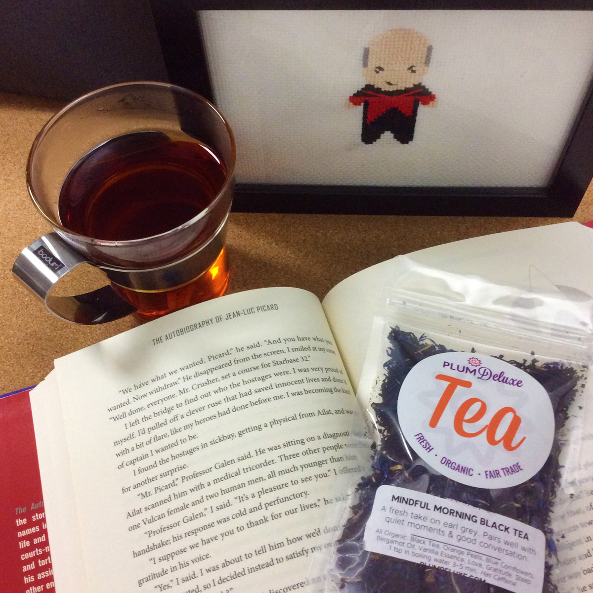 The Autobiography of Jean-Luc Picard lays open next to a cup of tea, a cross stitch of Picard, and a bag of loose leaf Earl Grey tea.