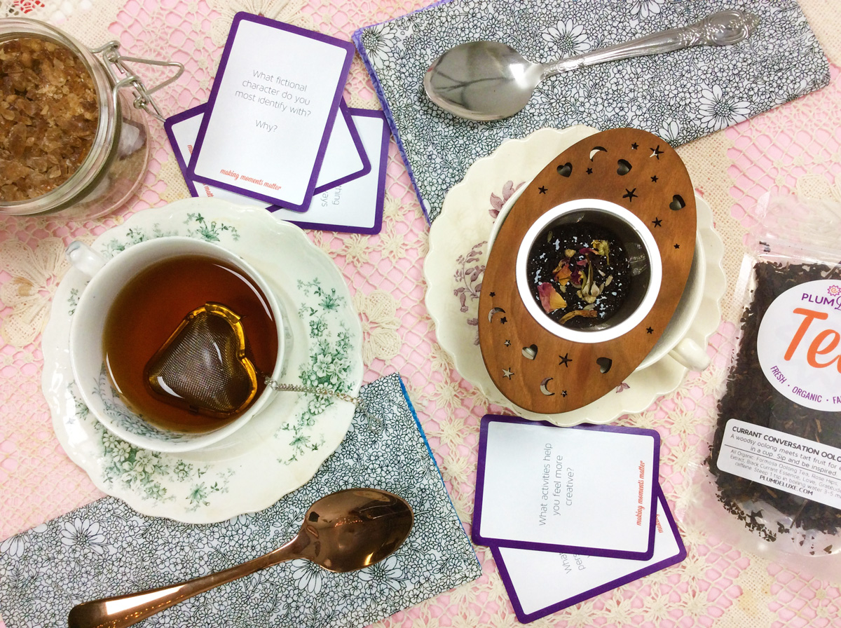 Overhead view of two teacups full of tea, tea infusers, teaspoons, sugar, and conversation prompts arranged on an array of pink, floral, and crochet lace linens.