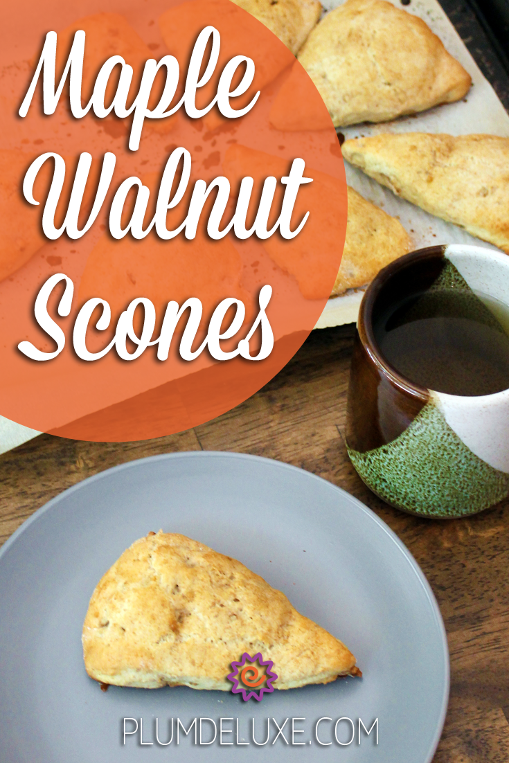 A wedge-shaped scone sits on a gray plate next to a green, brown, and white earthenware mug of tea and a tray of scones. The words read: Maple Walnut Scones.