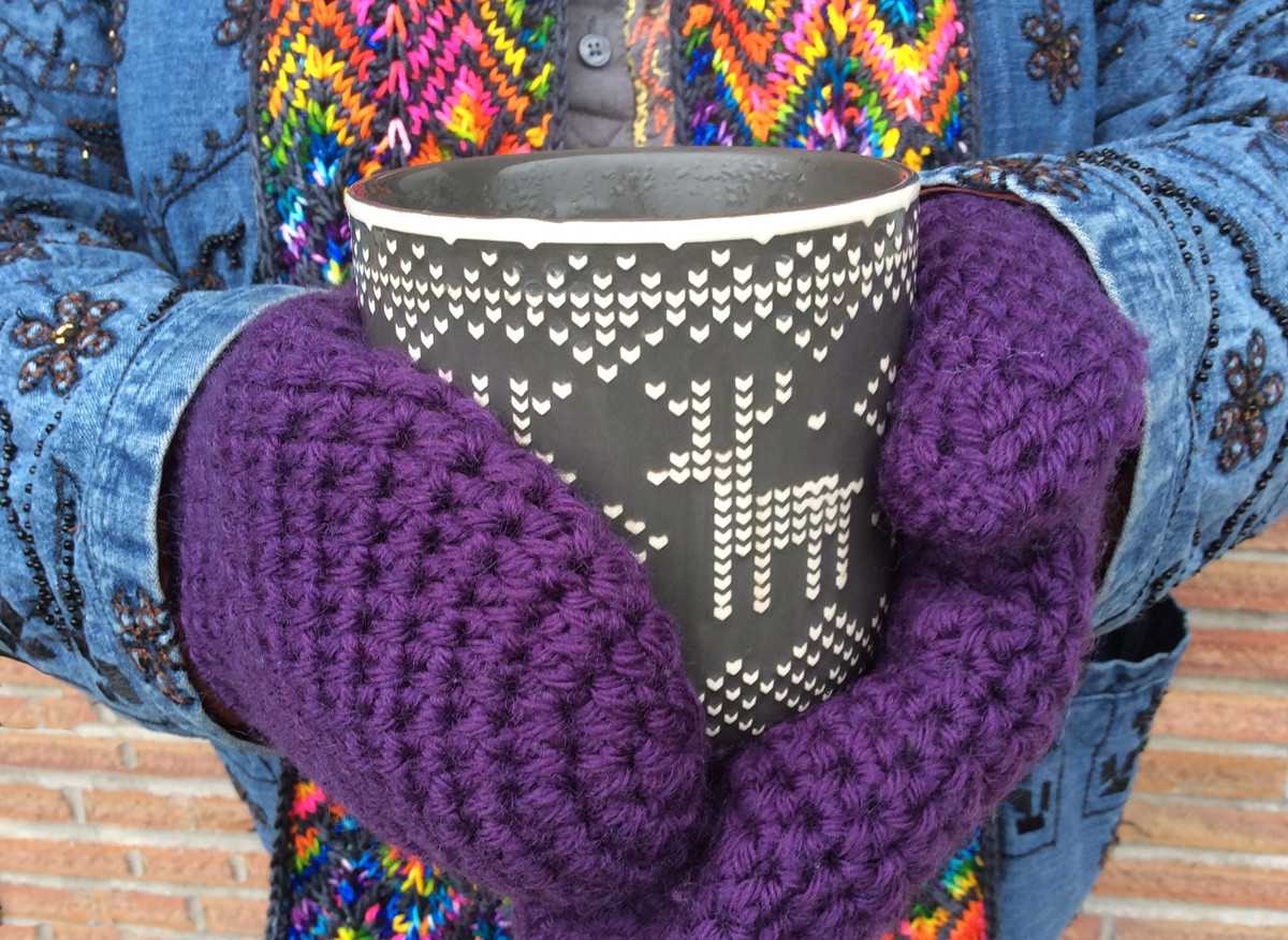 A pair of hands in purple crocheted mittens holds a large mug of tea with a nordic sweater pattern on it.