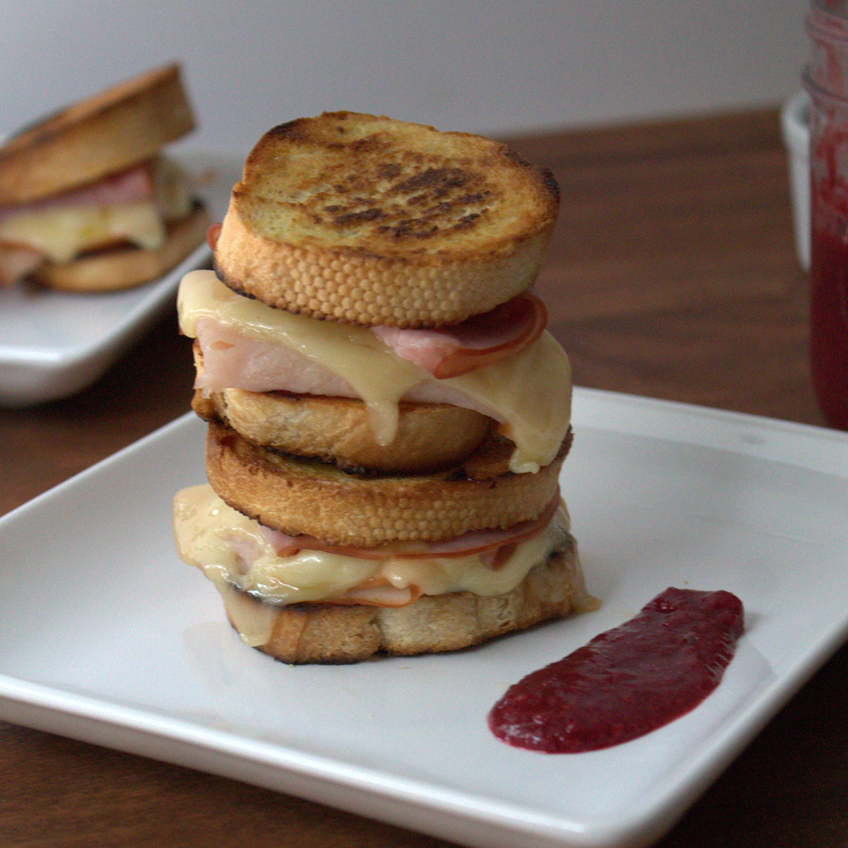 A stack of Monte Cristo tea sandwiches sits on a white square plate with a smear of jam.