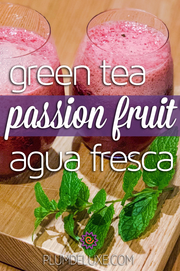 Two glasses of passion fruit agua fresca sit on a wooden cutting board along with a sprig of fresh mint.