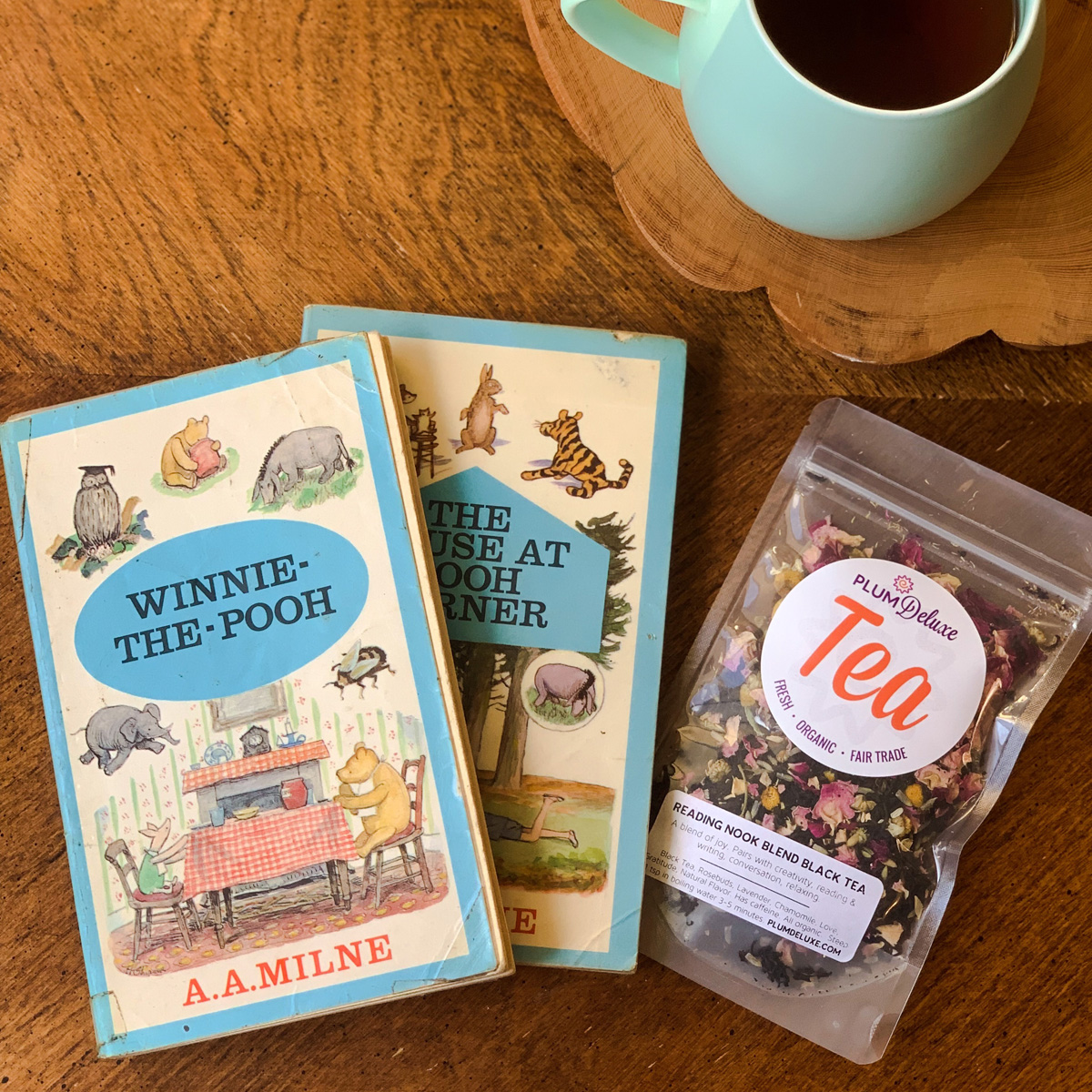 Overhead view of two Winnie the Pooh books, a bag of loose leaf tea, and a blue mug of tea arranged on a wooden table.