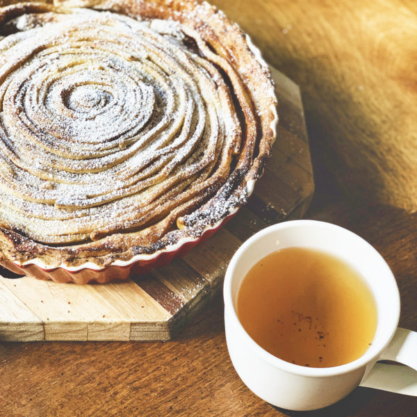 A white mug of tea sits next to a cinnamon swirl apple pie on a wooden table.