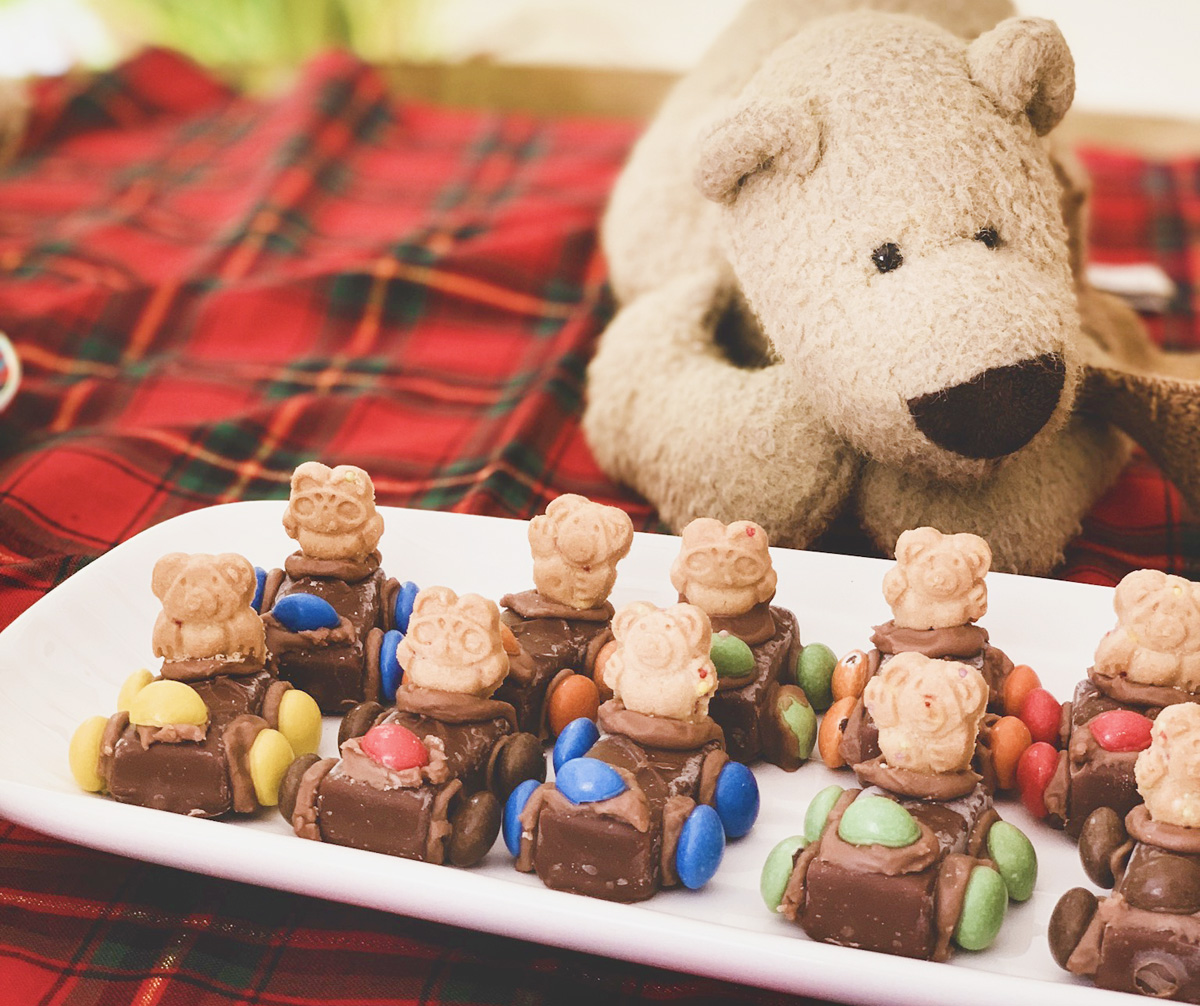 A white teddy bear is posed behind a plate full of candy and cookie teddy bear cars.