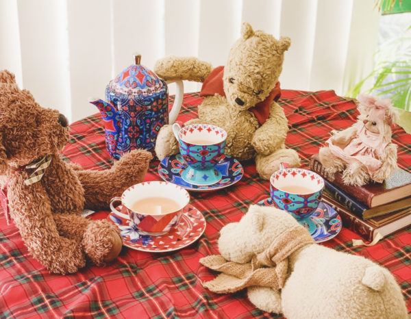 A group of four teddy bears are arranged on a red plaid blanket with brightly colored teacups in front of them.