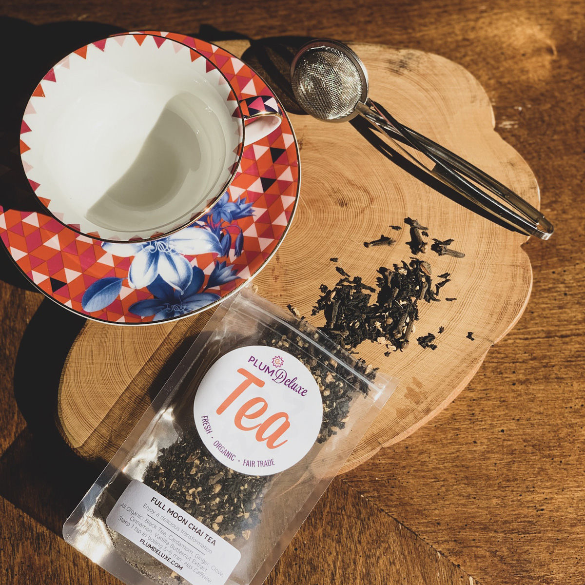 Overhead view of a red teacup, tea infuser, and bag of loose leaf chai on a wooden surface.