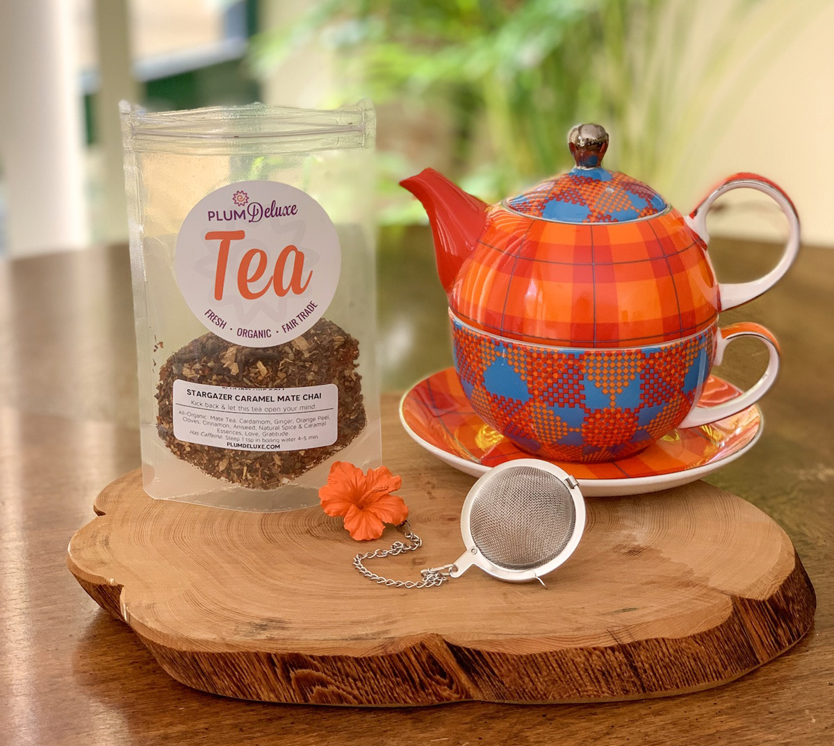 An orange and blue print teapot sits next to a bag of loose leaf herbal tea and a mesh tea ball infuser on a wooden slab.