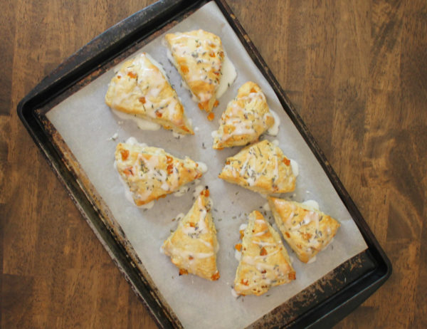 Overhead view of a parchment-lined baking tray full of eight baked apricot lavender scones.
