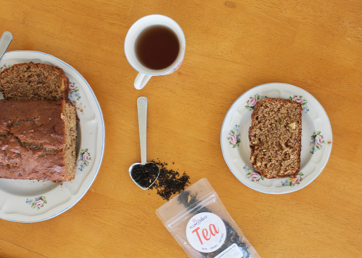Overhead view of a loaf of apple walnut bread, a cup of tea, a bag and scoop of loose leaf tea, and a slice of bread on a light wooden table.