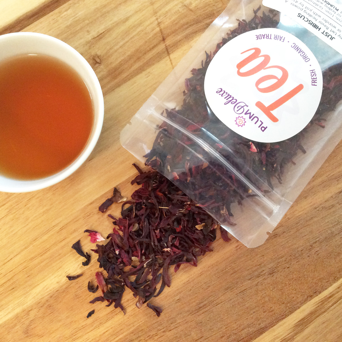 Overhead view of a bag of organic hibiscus herbal tea and a cup of tea on a wooden board.