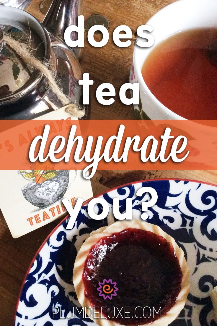 A floral mug full of tea sits next to a silver teapot and a blue and white plate with a jam tart. The words read: does tea dehydrate you?