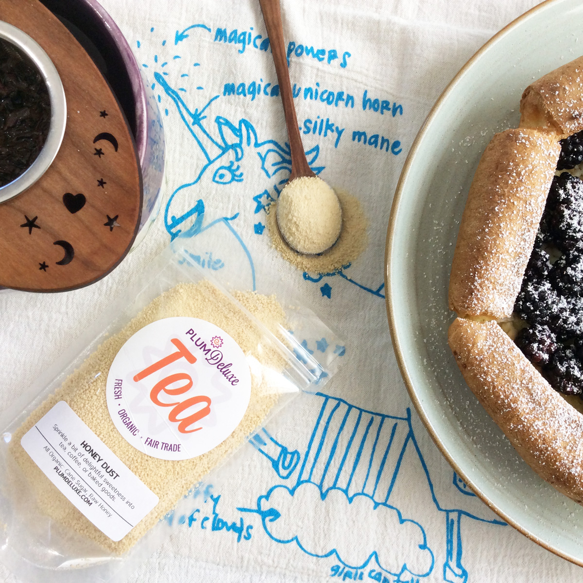 Overhead view of a bag of honey dust with a wooden spoon, a cup of tea with wooden infuser, and a plate with a dutch baby pancake on a unicorn tea towel.