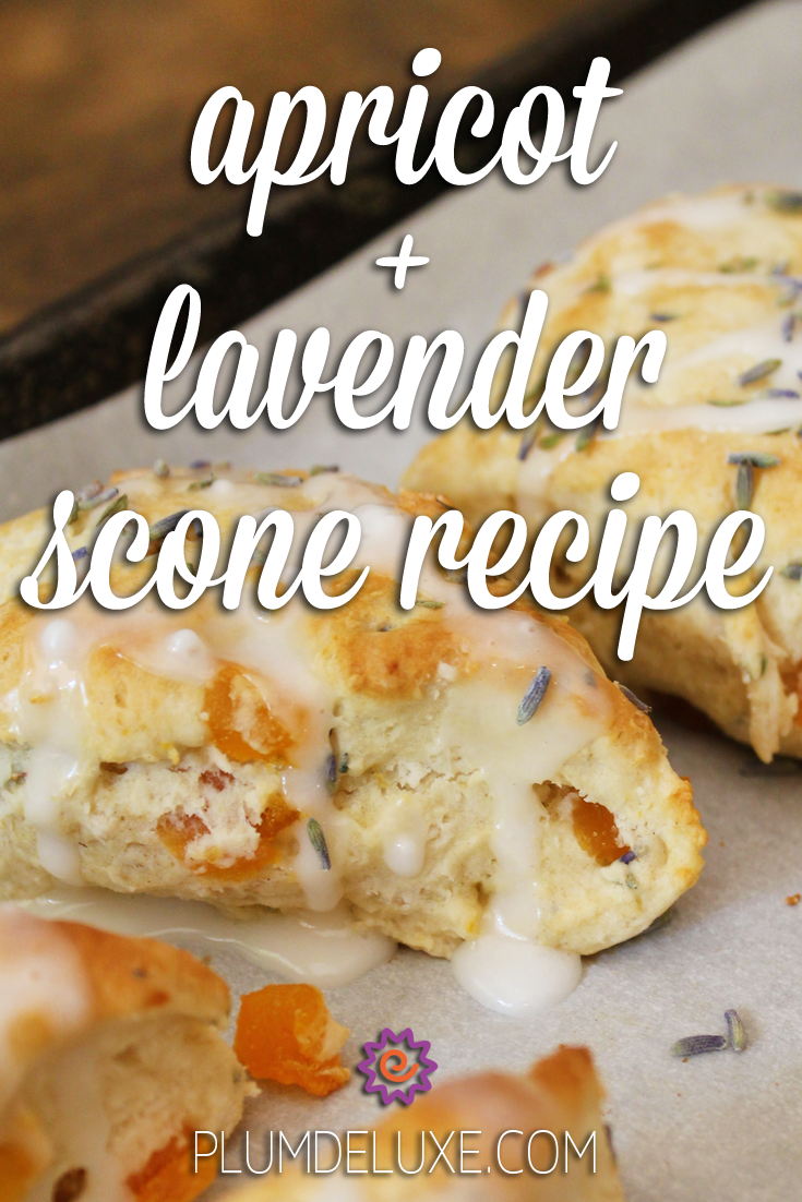 Closeup of apricot lavender scones with a sugar glaze on a parchment-lined baking sheet. The words read: apricot + lavender scone recipe.