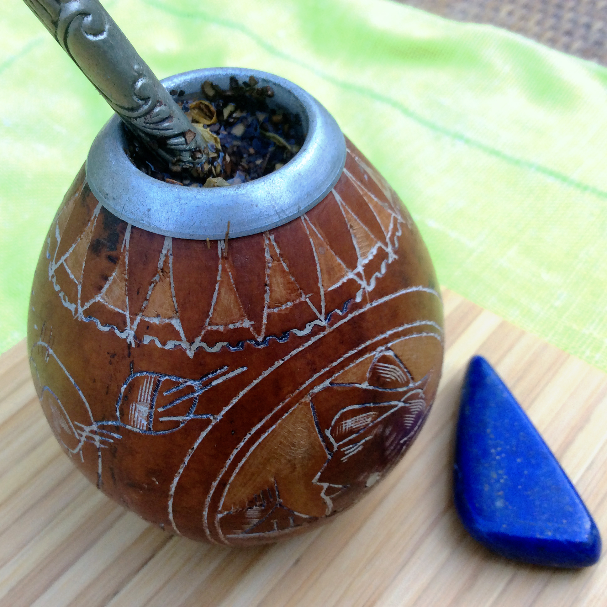 A mate gourd with a bombilla stuck in the opening sits on a wooden board next to a blue stone.