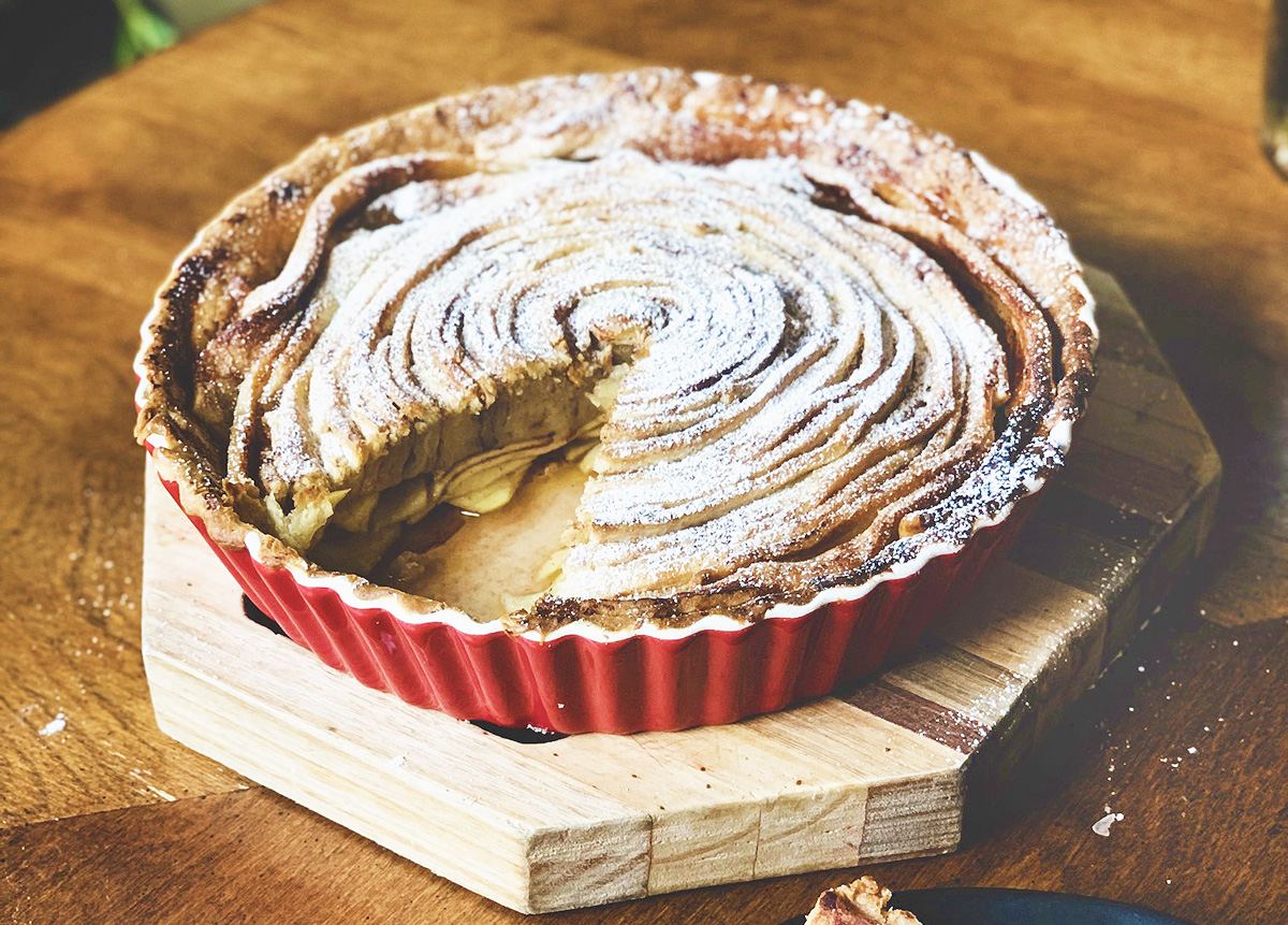 A cinnamon swirl apple pie in a red pie dish sits on a wooden board. A slice has been cut from the pie.