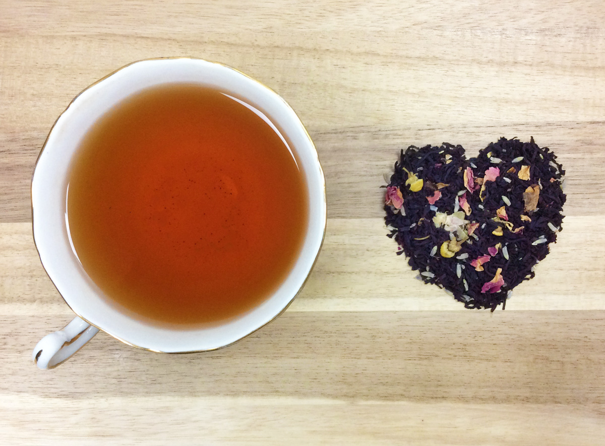 Overhead view of a cup of tea and a pile of loose leaf tea in the shape of a heart on a wooden surface.