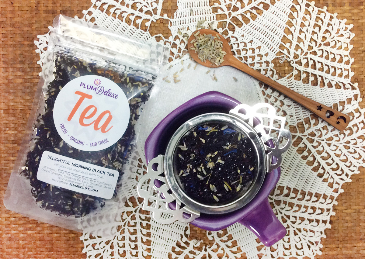 Overhead view of a purple mug of tea with a victorian tea infuser. A bag of Plum Deluxe Mindful Morning loose leaf tea and a wooden spoon sit next to it on a white lace doily.