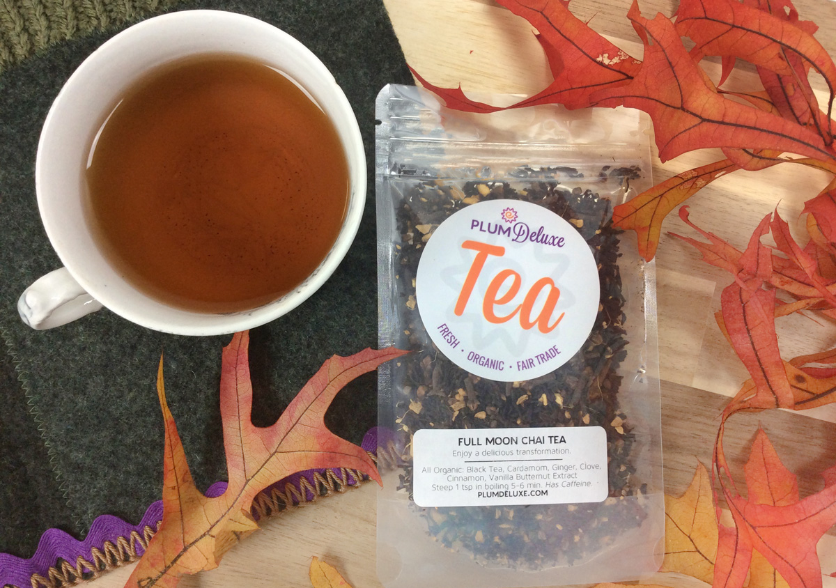 Overhead view of a bag of Plum Deluxe Full Moon Chai with a white mug of brewed chai surrounded by orange fall leaves.
