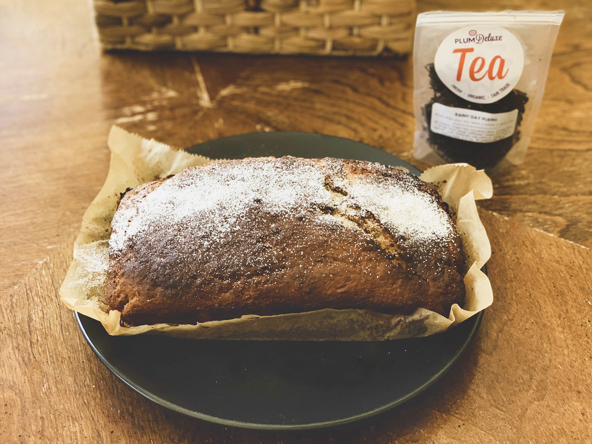 A loaf of spiced banana bread sits on a plate next to a bag of Plum Deluxe loose leaf tea.