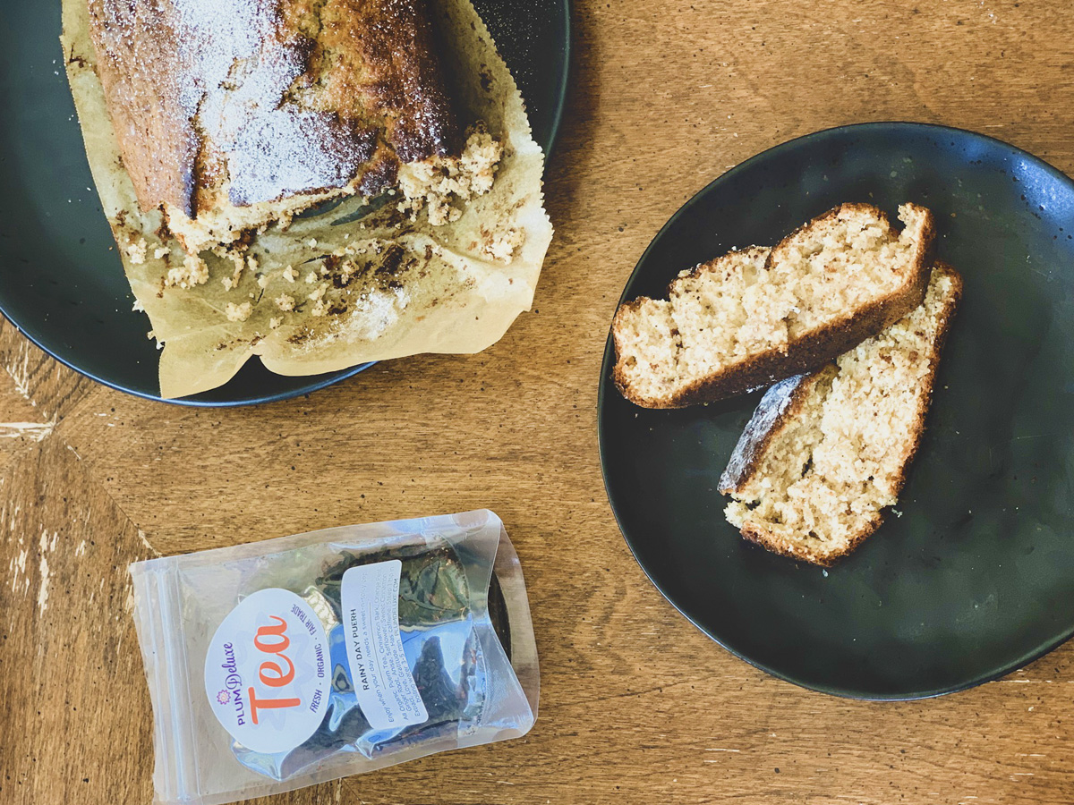 Overhead view of a loaf and two slices of spiced banana bread along with a bag of plum deluxe loose leaf tea on a wooden table.