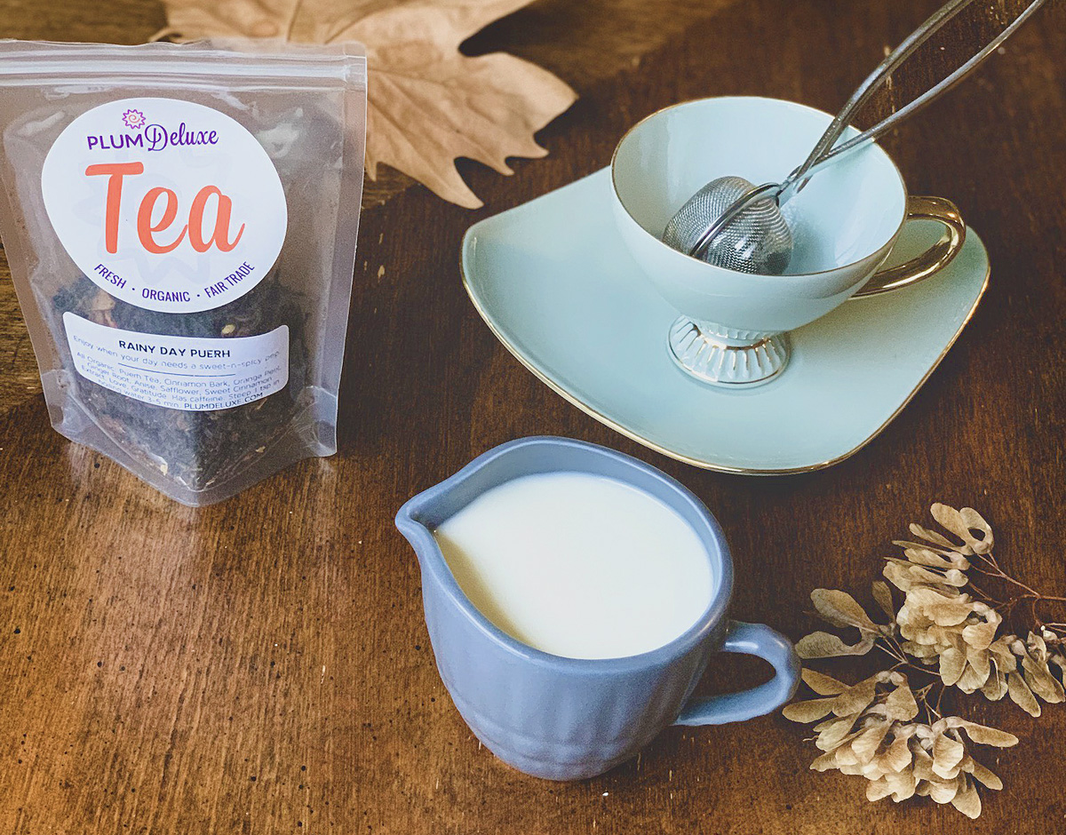 A light blue pitcher of pumpkin spice creamer sits on a wooden table next to a teacup and saucer and a bag of loose leaf tea.