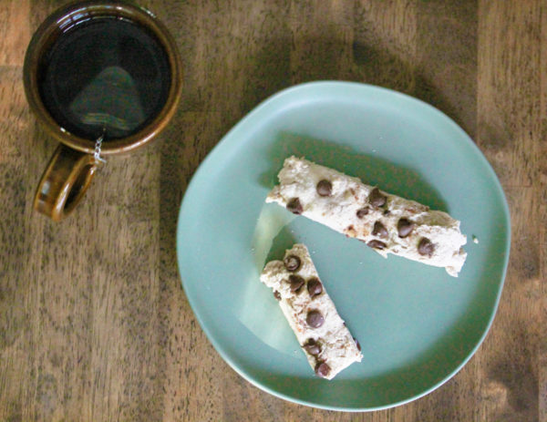 Overhead view of two cinnamon chip scone sticks on a light blue plate next to a brown earthenware mug of tea on a wooden table.