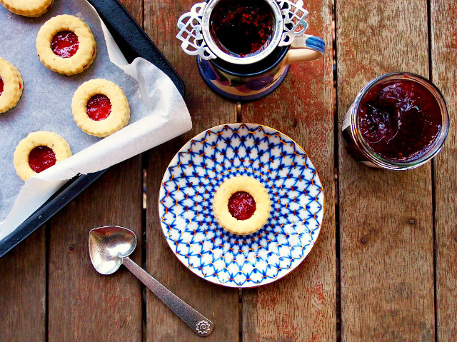 Overhead view of homemade jammie dodgers on a baking tray and a blue and white plate, with a heart-shaped spoon, cup of tea with Victorian tea infuser, and jar of jam on a wooden table.